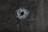 picture of gunshot  - Bullet hole in glass on dirty grungy black background - JPG