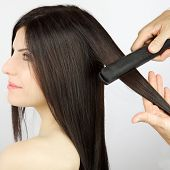Woman Getting Hair Straightened After Trim At Professional Salon