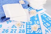 stock photo of menses  - Sanitary pads and white flowers on blue calendar background - JPG