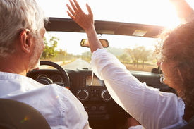 foto of maturity  - Mature Couple Driving Along Country Road In Open Top Car - JPG