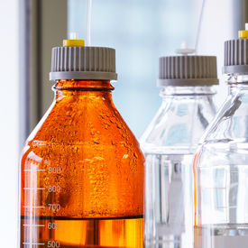 stock photo of chromatography  - Close up clear and amber color bottle with plastic hose for High performance liquid chromatography  - JPG