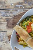 stock photo of curry chicken  - Bowl with curry flavored rice chicken and vegetables on rustic wooden table