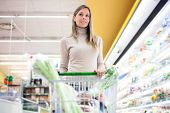 stock photo of grocery store  - Woman pushing a shopping cart in a grocery store - JPG