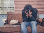 picture of sad  - A sad and depressed young man is sitting on a sofa with a cat and his head buried in his hands