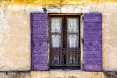 foto of lace-curtain  - Charming Lace Curtained Window in old wall in Provence with violet shutters against textured ocher wall - JPG