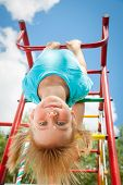 stock photo of monkeys  - Portrait of cute blond girl with blue eyes wearing blue tshirt sitting on monkey bars on a summer day - JPG