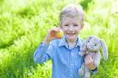 stock photo of easter eggs bunny  - smiling little boy holding easter egg and bunny after egg hunt at spring time - JPG