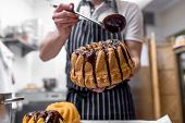 foto of pinafore  - Man pouring hot chocolate on Easter cake - JPG