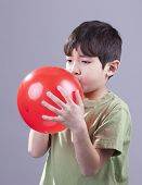 stock photo of blow-up  - A young boy blows up a red baloon - JPG