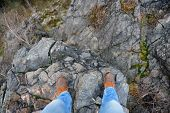 stock photo of edging  - man standing on edge of a cliff - JPG