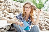 picture of dreadlock  - Young cheerful stylish girl with dreadlocks outdoors - JPG