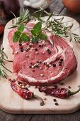 stock photo of ribeye steak  - Raw ribeye steak on wooden board with peppercorn and rosemary - JPG