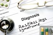 stock photo of willy  - Diagnosis Restless legs syndrome and tablets on a wooden table - JPG