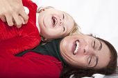 foto of santa baby  - tender and funny portrait of one year age caucasian blonde cute lovely baby Santa Claus Christmas disguise with brunette woman mother red cardigan green sweater embraced laughing together lying on white floor background - JPG