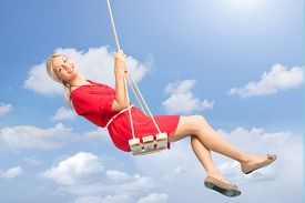 picture of swing  - Beautiful blond woman swinging on a wooden swing outdoors on a beautiful summer day  - JPG