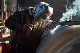 image of welding  - welder brews manual arc welding a workpiece of large diameter pipe - JPG