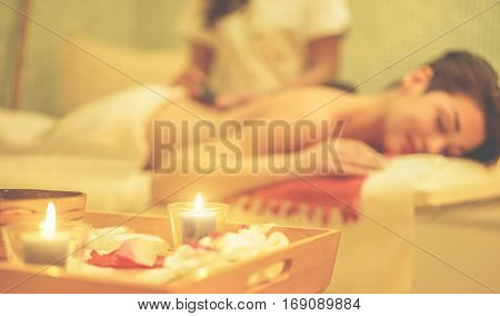 poster of Young woman having hot stone therapy massage in spa resort hotel salon - Female enjoying relaxing back massage - Body care skin care wellness concept - Focus on right candle - Warm cinematic filter