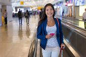 Travel woman using smartphone at airport. Young asian traveler holding mobile phone app in terminal  poster