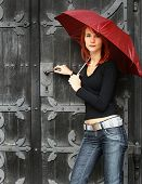 beautiful girl under rad umbrella near the old door