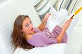 Shocked pretty woman sitting on sofa at home and holding letter in hands