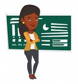 African-american young teacher standing in classroom. Smiling teacher standing in front of chalkboar poster
