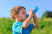 stock photo of drinking water  - Little boy drinking gas water on green grass field - JPG