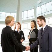 Geschäftsleute, die ihre Hände schütteln, zwei Geschäftsfrauen anschauen