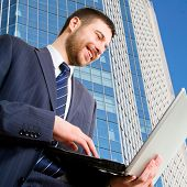 Walking businessman using his lap-top against a  skyscraper