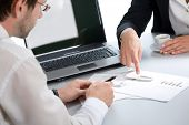 Image of two business partners discussing documents lying on the table