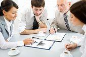 Retrato de empresarios sentados alrededor de la mesa y mirando de documento