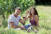 Couple of winegrowers drinking wine in vineyard