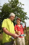 Senior couple rambling in countryside with map