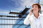 Businesswoman on the phone in front of building