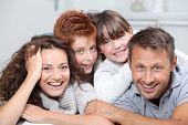 Glückliche Familie mit 4 Personen auf einem Sofa zu Hause