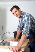 Plumber fixing domestic sink poster