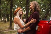 Beautiful hippy couple man and woman smiling and hugging each other while walking in forest poster