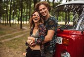 Attractive hippy couple man and woman smiling and hugging each other while standing near minivan in  poster