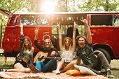 Group of friends hippies men and women laughing and sitting near vintage minivan into the nature poster
