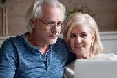 Close Up Of Aged Husband And Wife Relax With Laptop poster