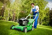pic of grass-cutter  - lawn mower man working on the backyard - JPG