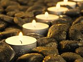 burning candles in the row on the stones