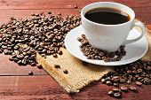 stock photo of wooden table  - white cup with coffee beans on the wooden table - JPG