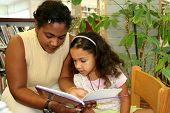 stock photo of storytime  - Child in a school library with teacher - JPG