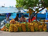 MALE - JULY 1: Three street vendors sit by bananas stall - Market situated on the harbor of Male - c