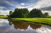Idyllic golf course with reflection in the river