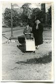 Vintage photo of mother and son pushing a pram (early fifties)