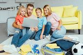 Happy Family Using Laptop, Planning Summer Vacation, Packing Luggage And Having Great Time, Travel C poster
