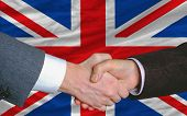 Businessmen Handshake After Good Deal In Front Of Uk Flag