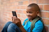 Happy african student wearing green bagpack and using smartphone at school. Smiling cute boy playing poster