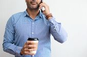 Closeup Of Business Man Talking On Phone And Holding Drink. Person Standing And Having Break. Commun poster